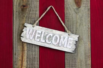 Welcome sign hanging on wooden door