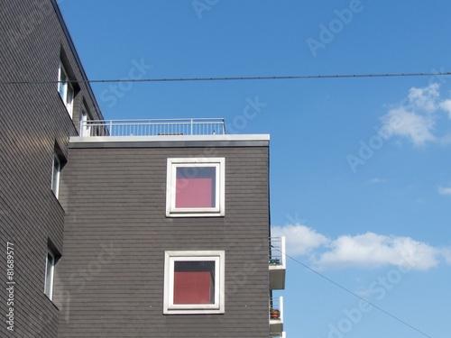 fenster mit roten gardinen in einer grauen fassade in. Black Bedroom Furniture Sets. Home Design Ideas
