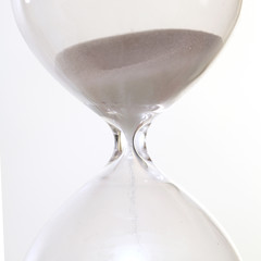 Sand passing through the glass bulbs of an hourglass