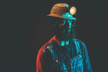 Male Miner Wearing Helmet Lamp Staring to the Side