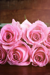 Vintage style pink roses on rustic dark wood table.