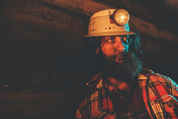 Miner Wearing Helmet Lamp and Leaning Against Wall