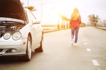 Upset blonde woman leaving her broken roadster