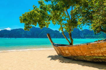 Wooden boat on the sandy shore of the exotic beach