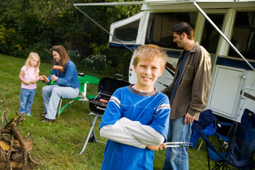Camping: Boy Helps Father Cook Dinner On Grill By Camper