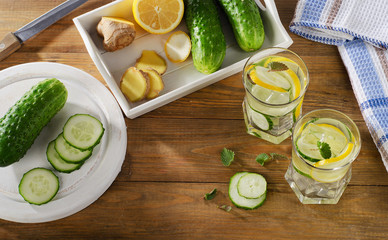 Fresh water with lemon and cucumber  on wooden background.