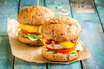 two home burgers with fresh vegetables and chicken cutlets
