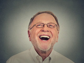 Laughing senior man isolated on gray background