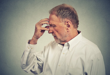 Thoughtful senior man on gray wall background