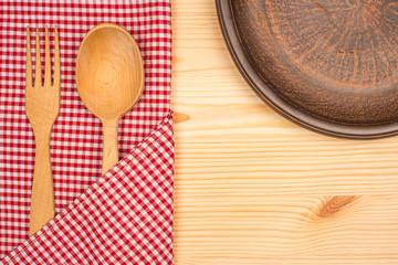 Kitchen tablecloth, fork, spoon on wooden table background