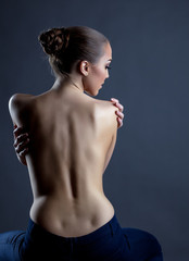 Rear view of slim model posing with naked back
