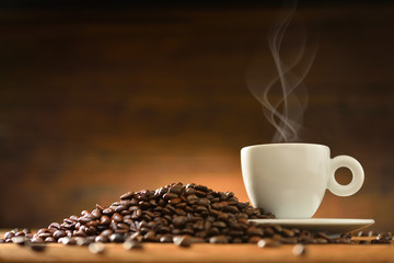 Cup of coffee with smoke and coffee beans on  wooden background