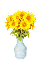 Bouquet of bright yellow sunflowers with an old blue jug