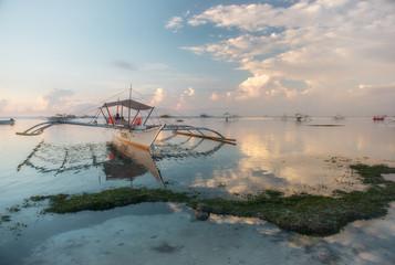 Boats on a tropical beach at sunrise
