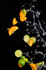 Limes and oranges with water splashes on black