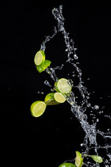 Limes with water splashes on black background