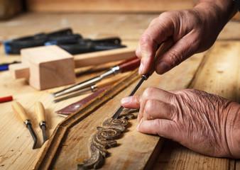 Close up of senior carpenter hands restoring old furniture with chisel.