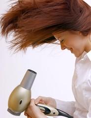 Junge schöne Frau föhnt sich wild die Haare
