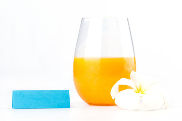 Fresh orange juice glass with white flower and blank tent note o