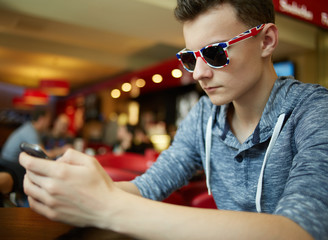 Teenager boy with smartphone in a restaurant