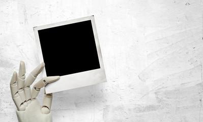 Closeup of white wood hand with polaroid frame