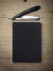 Straight razor and black paper on wood desk