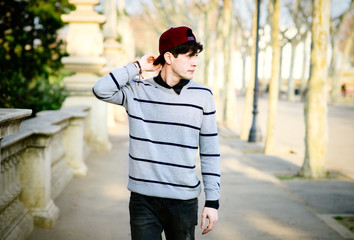 Young trendy hipster in red cap walking in the park