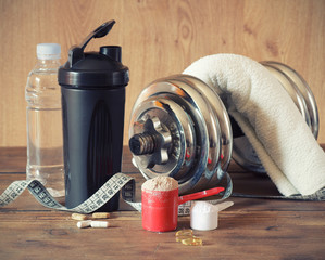 Whey protein powder in scoop with vitamins and plastic shaker