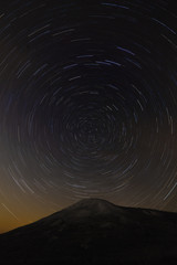 Trail of stars around the pole star on top of the mountain backg