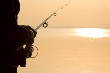 Tuinposter Vissen Fisherman silhouette at sunset near the sea with a fishing rod