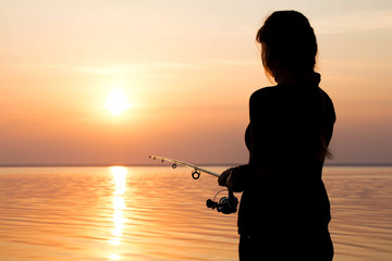 Wall Murals Fishing silhouette of a girl on the bank of the river with a fishing rod