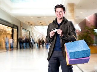 Smiling handsome man with shopping bags and credit card
