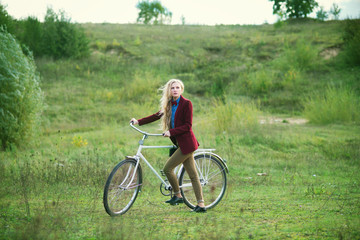 The beautiful blonde on a bicycle in the spring