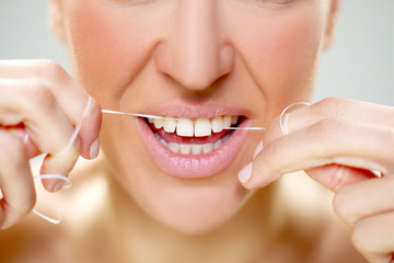 woman cleaning tooth with floss