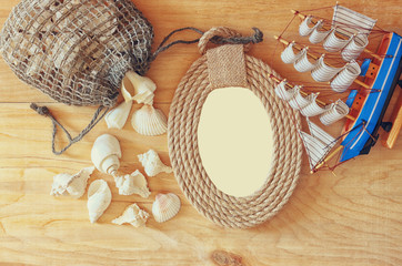 Top view of vintage nautical frame from ropes, wooden boat and n