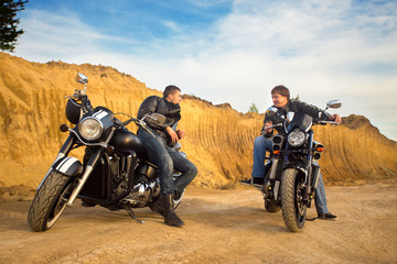 Two bikers on unknown motocycles talking on desert road Fototapete