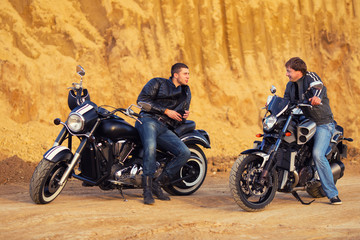 Two bikers on unknown motocycles talking on desert road