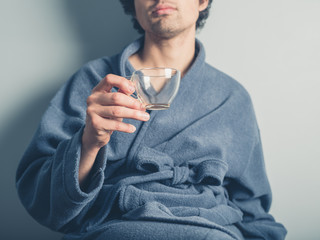Man in bathrobe with empty cup