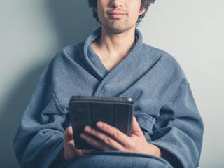 Man in bathrobe using tablet