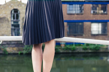 Woman wearing skirt standing on bridge by canal