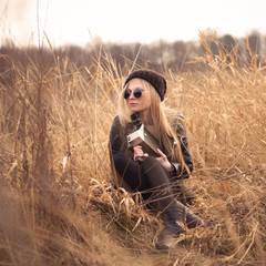 hipster beautiful girl with the camera in a field in spring
