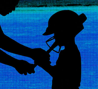 Coach helping young ball player