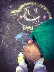 Kid is drawing on the street with chalk