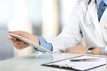 Doctor working with tablet computer.  Prescription on a table be