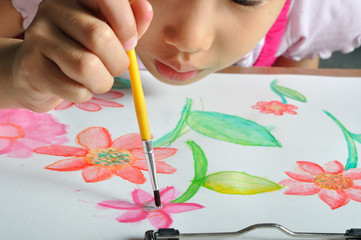 closeup little asian girl hand paint her watercolor picture