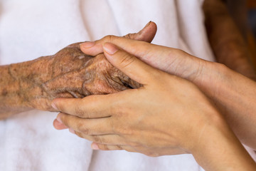 Hand of woman touching senior woman in clinic.