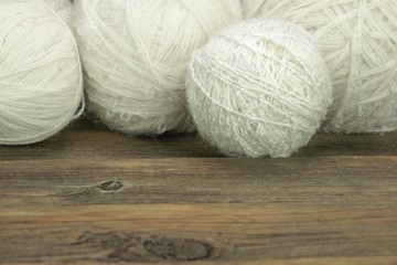 White Wool Rolls On Wood Background