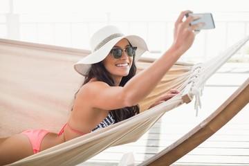 Pretty brunette relaxing on a hammock and taking selfie