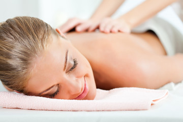 Young woman having back massage on spa treatment