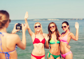 group of smiling women photographing on beach